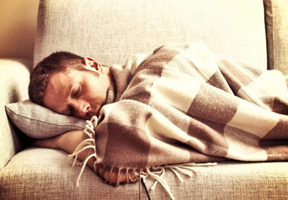 Young man tired and sleeping on the sofa.